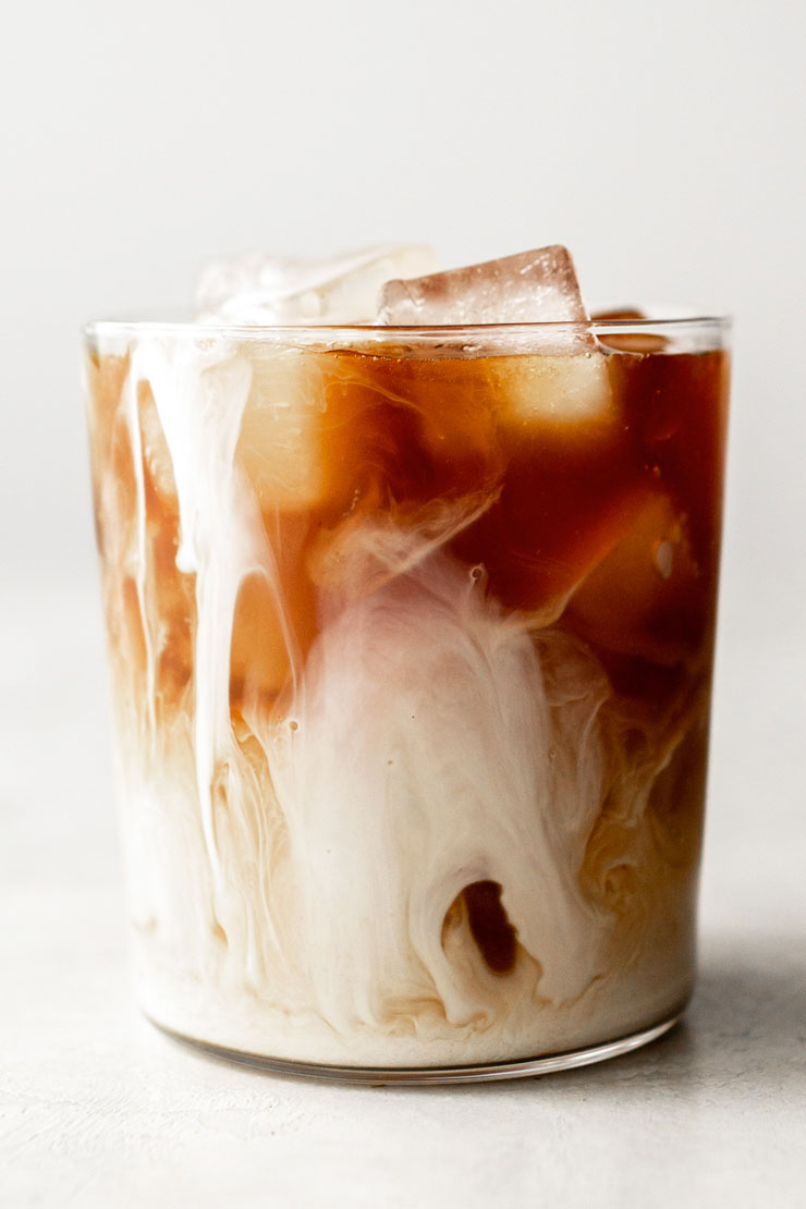 Iced cold brew coffee in a cup with half & half.