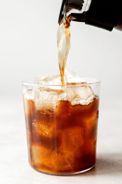 Pouring cold brew coffee into a glass filled with ice.