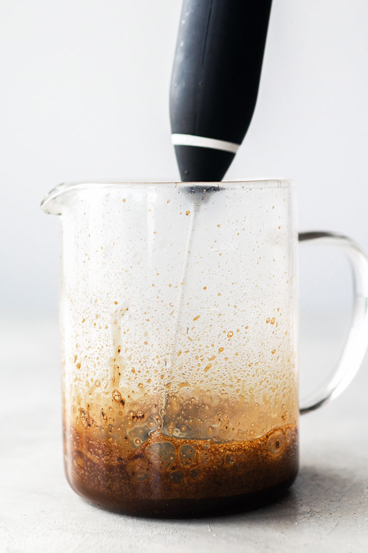 Whisking instant coffee, sugar, and water in a glass container.