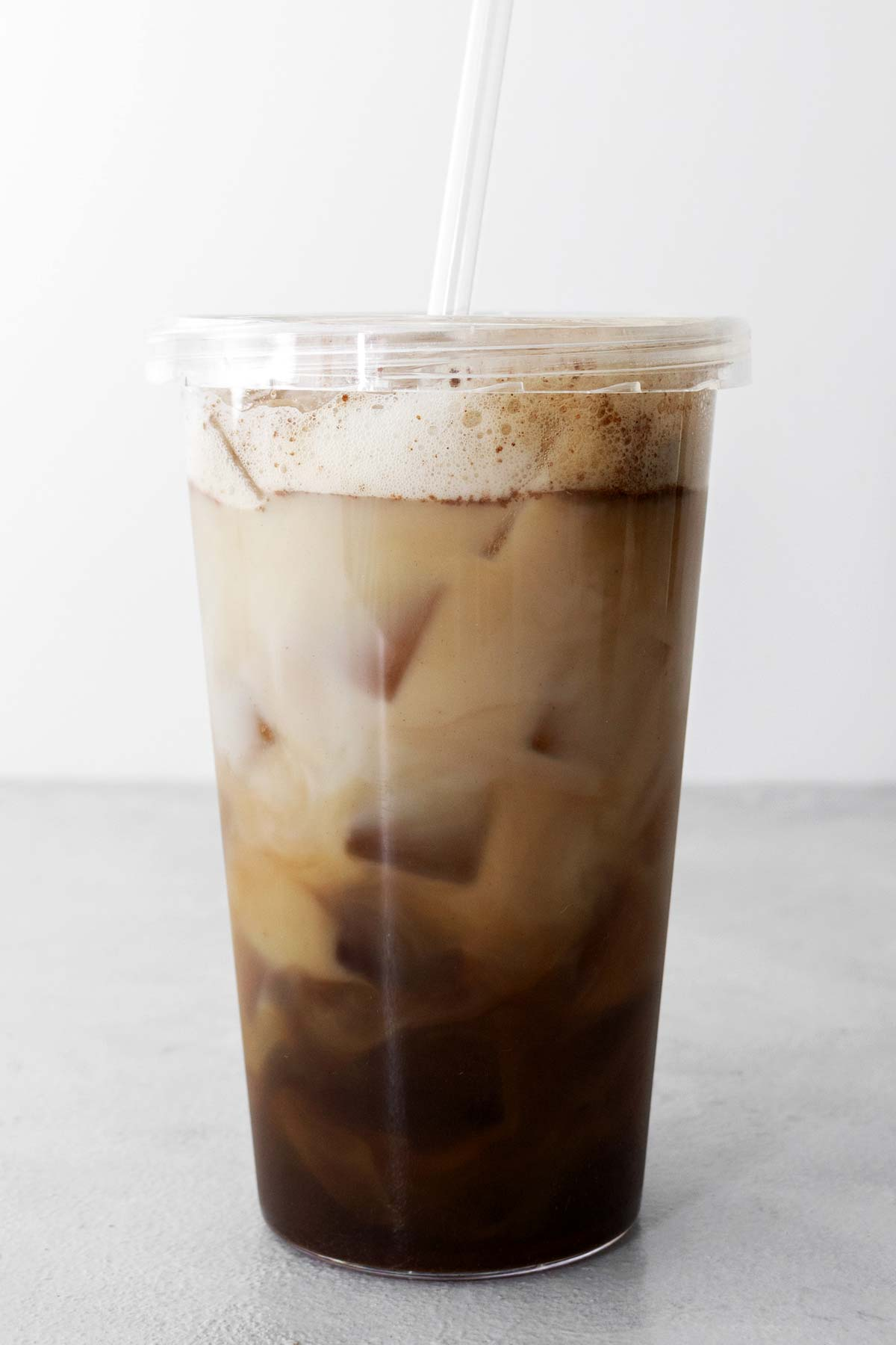 Starbucks Iced Brown Sugar Oatmilk Shaken Espresso copycat drink in a cup with lid and straw.