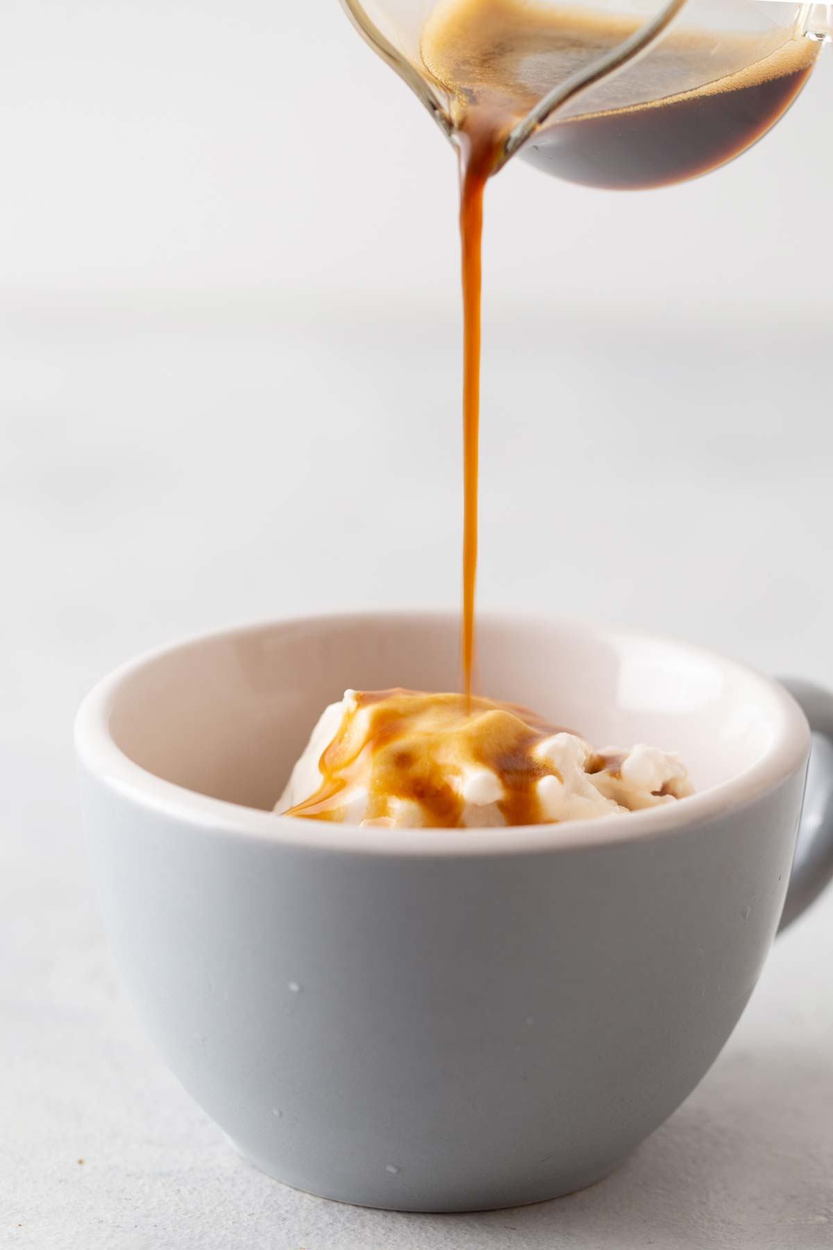 Pouring espresso into a small mug of ice cream to make an affogato.