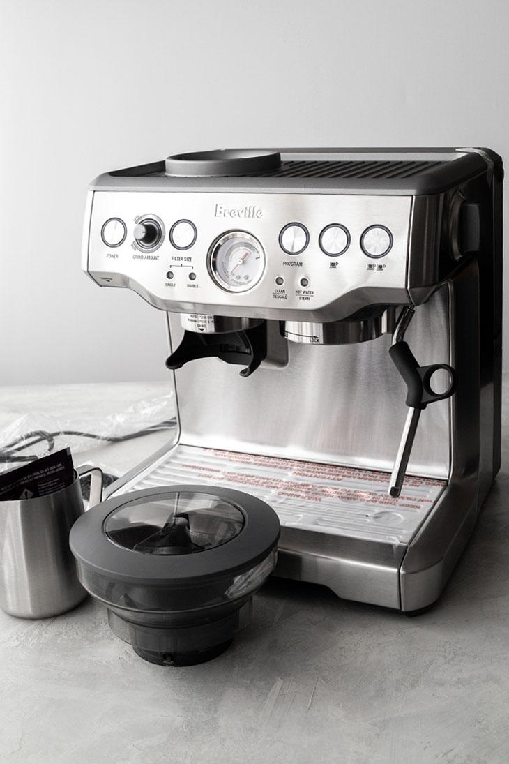 Brand new Breville Barista Express espresso machine on a table.