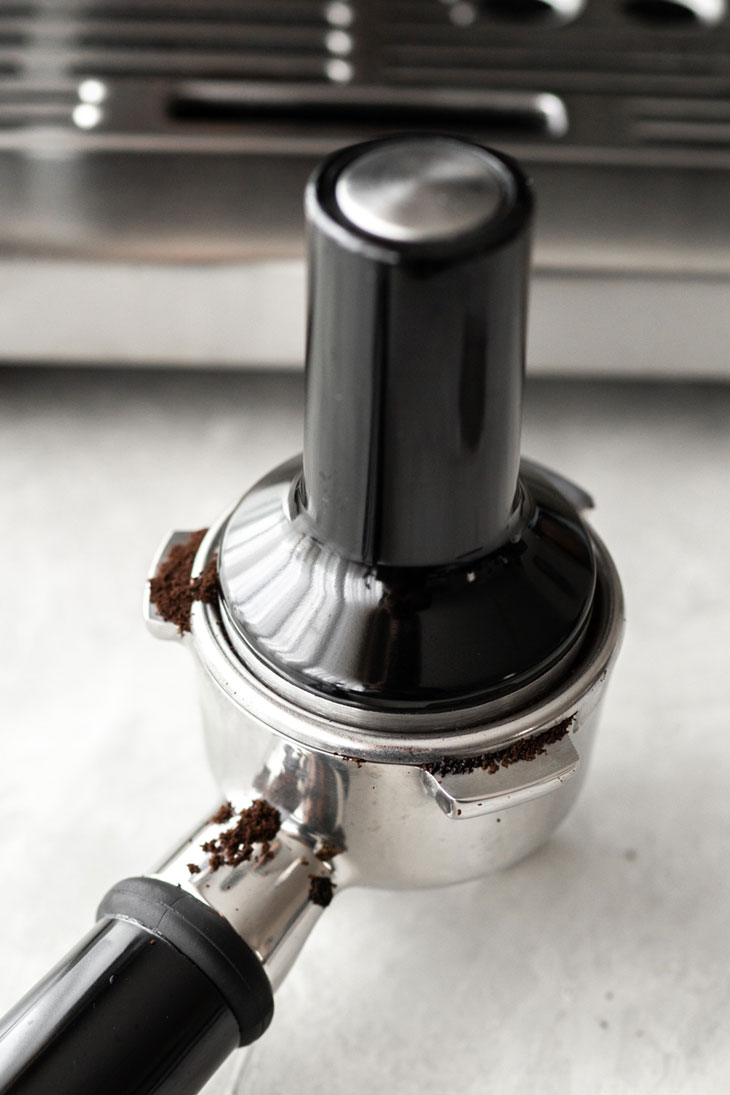 Tamping down ground coffee into a portafilter.