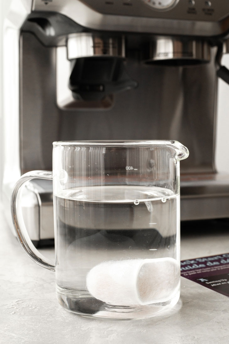 Soaking water filter in a glass of water.