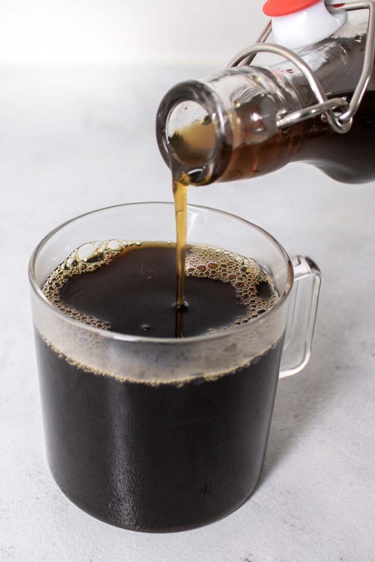 Pouring brown sugar syrup into a cup of coffee.