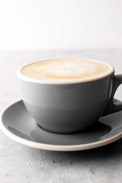 Cafe au lait in a gray cup with saucer.