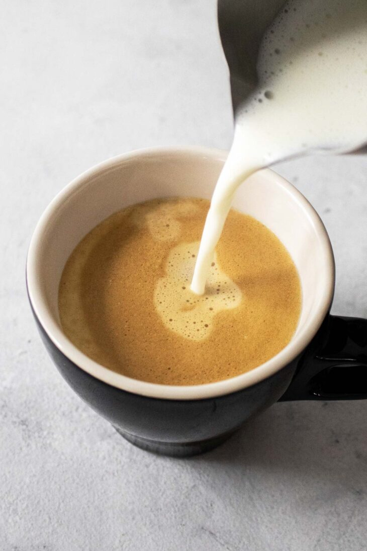 Pouring frothed milk into a cup with espresso.