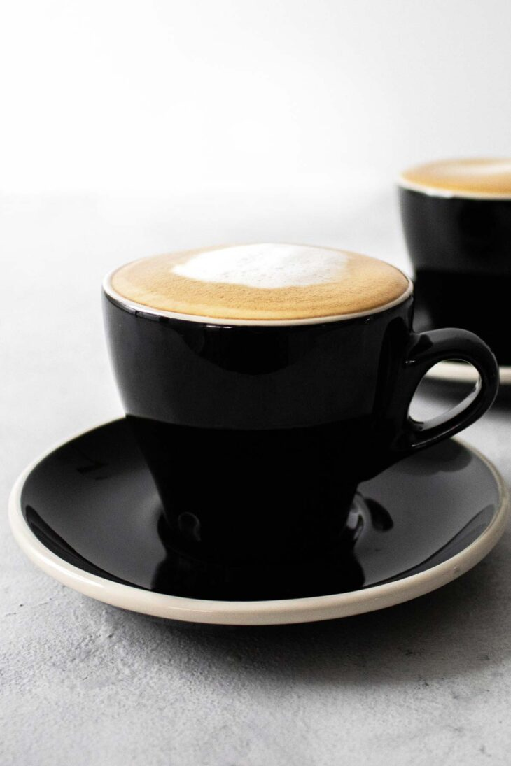 Two black cups with saucer filled with cappuccino.
