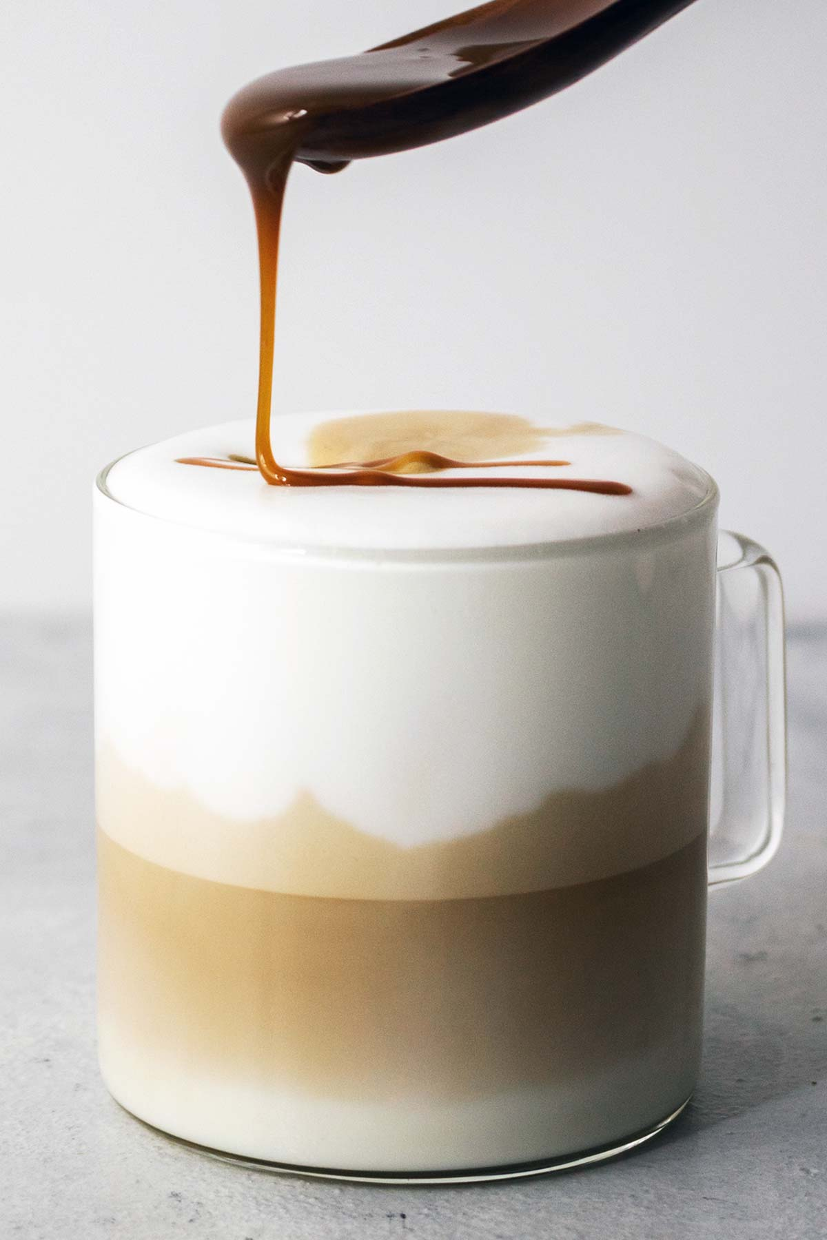 Drizzling caramel sauce on top of a Caramel Macchiato drink.