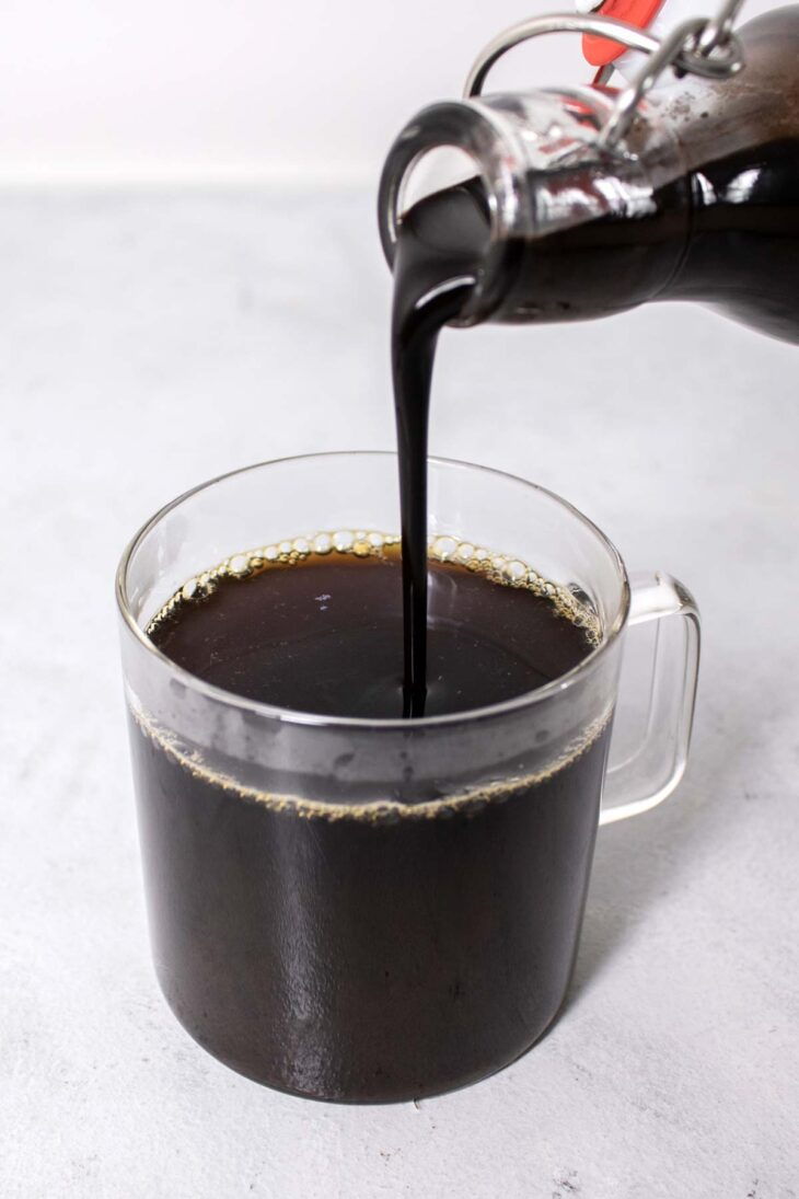 Pouring chocolate syrup into a cup of coffee.