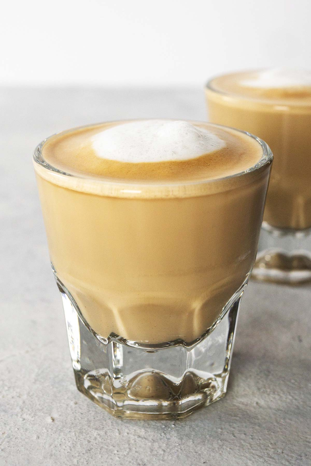 Two cortado drinks in glass cups.