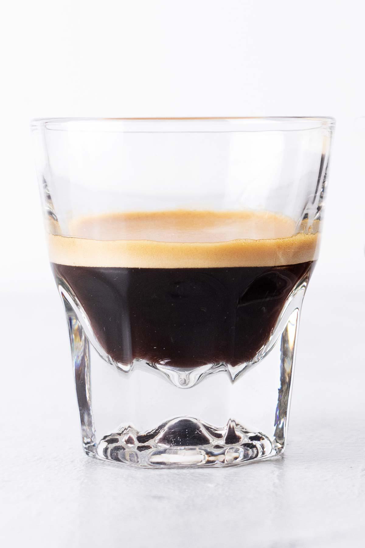 Small glass of espresso with crema.