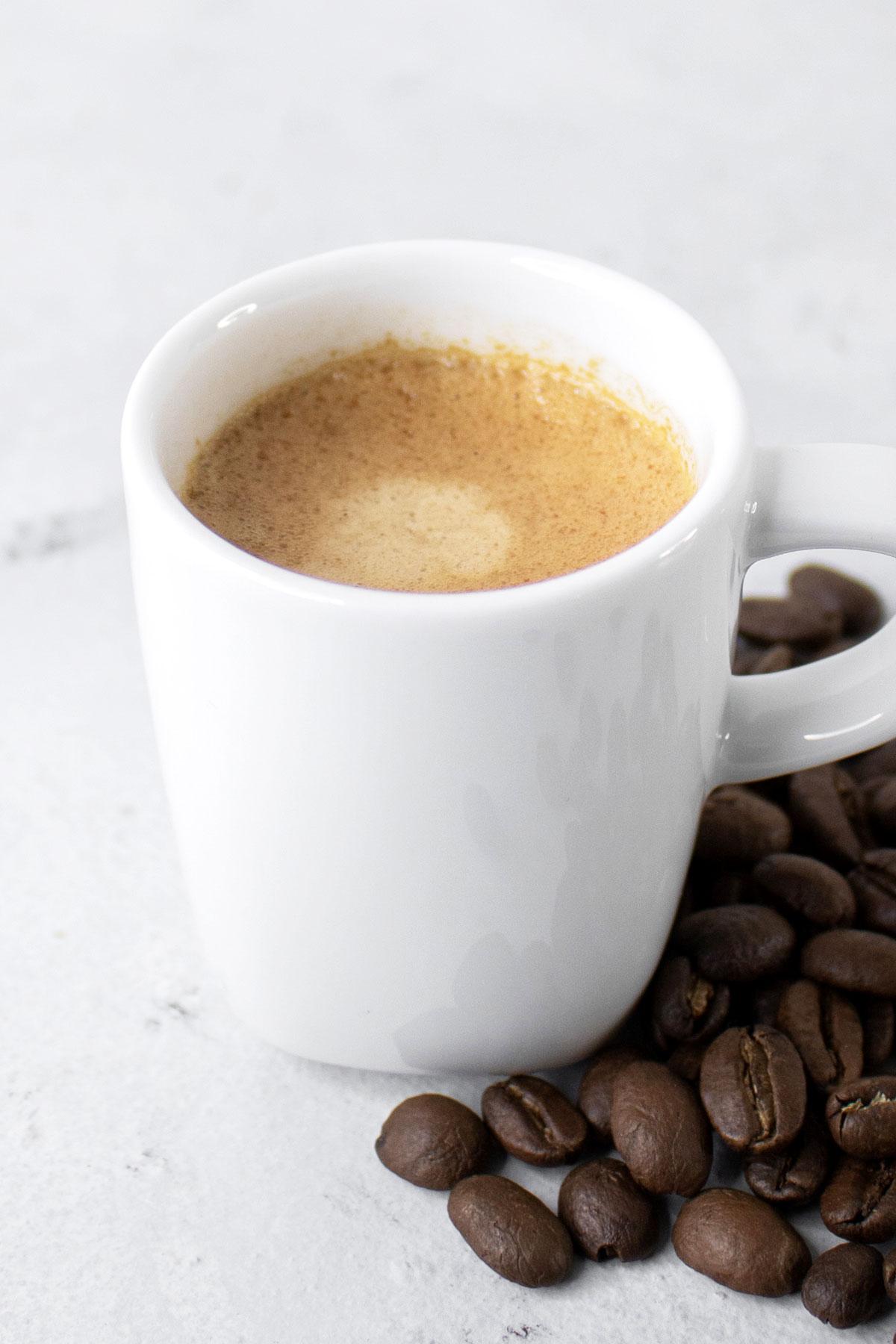 Espresso coffee in a small white mug.