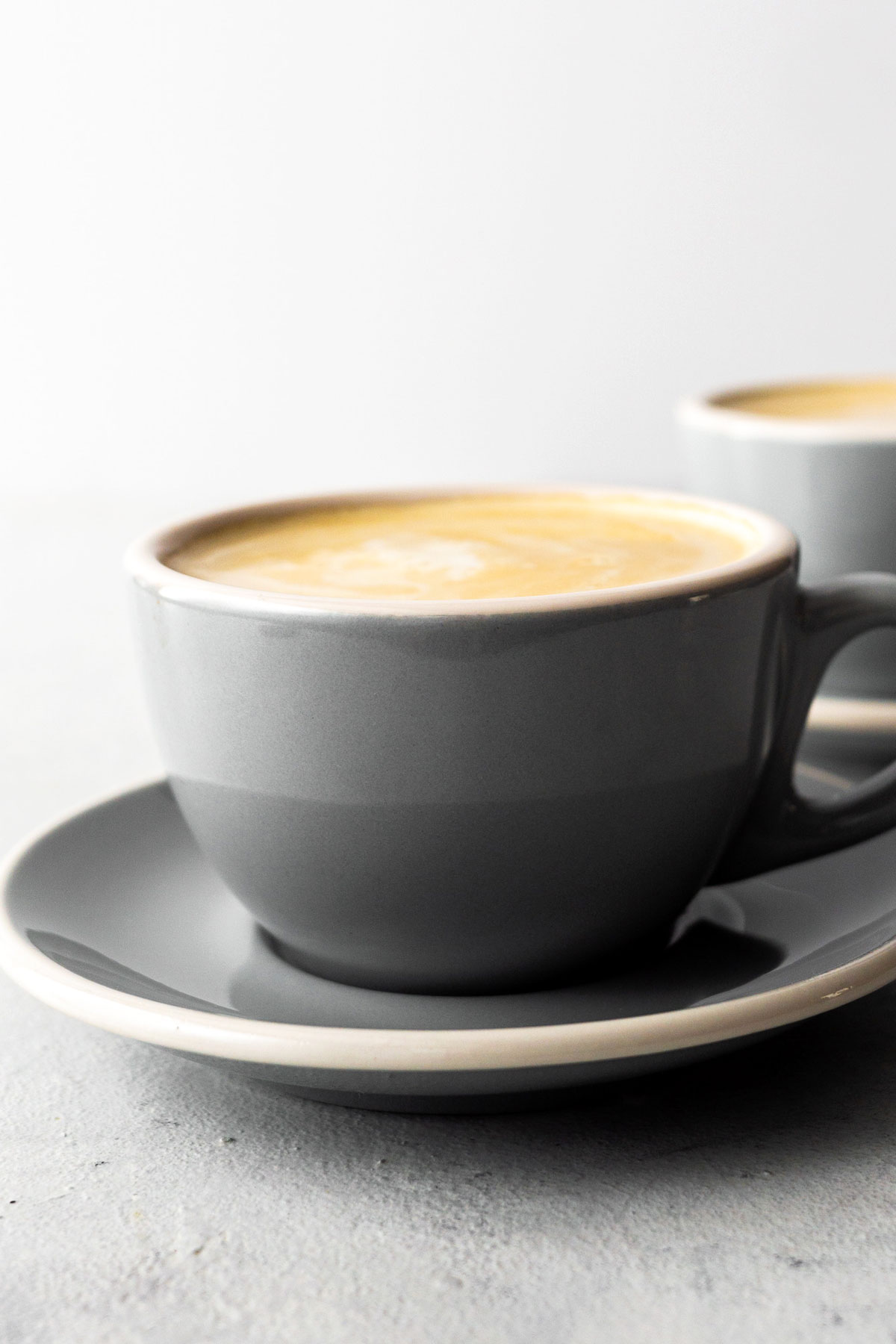 Flat white drink in a gray ceramic cup with saucer.