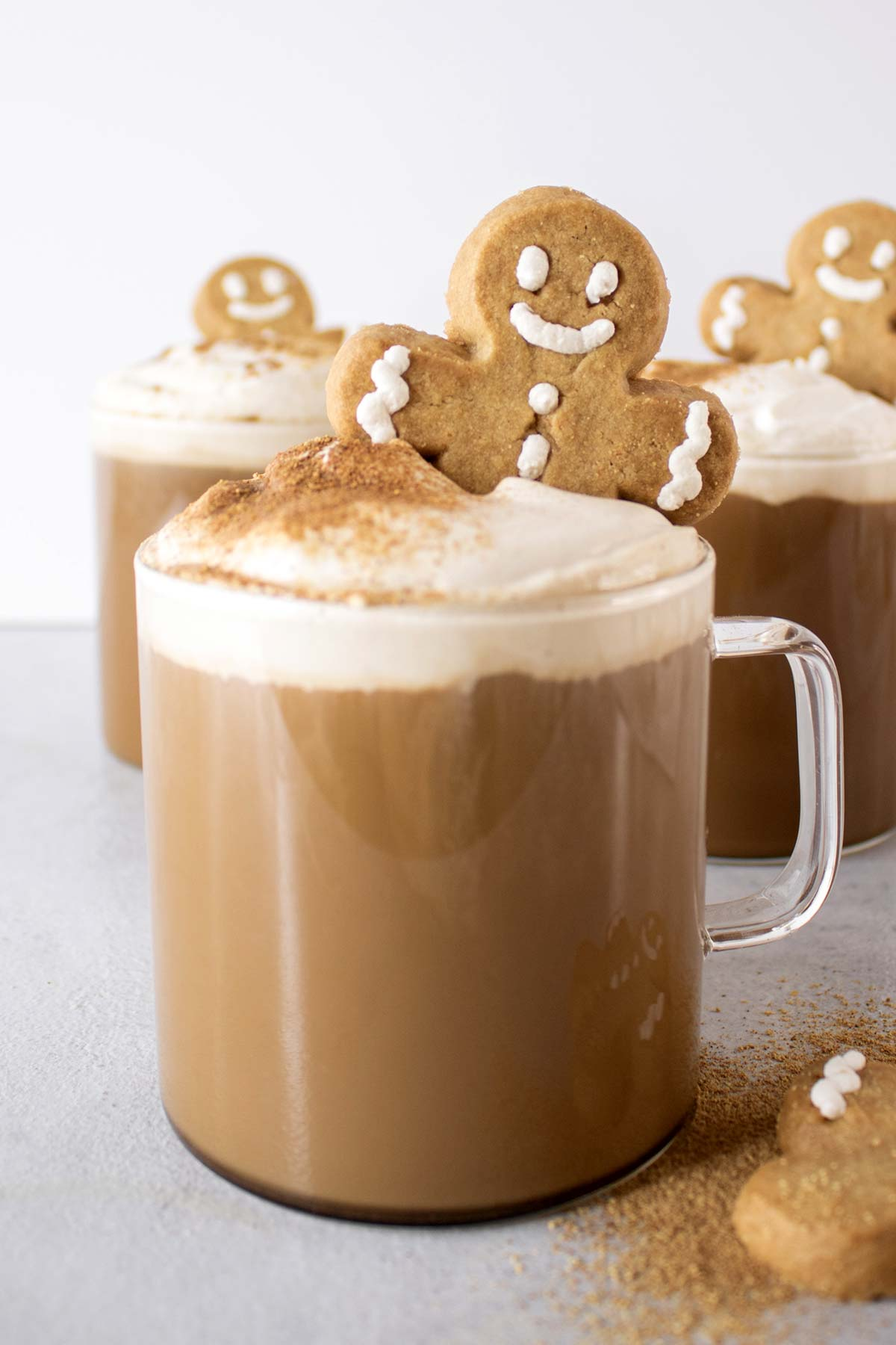 Gingberbread lattes topped with whipped cream and gingerbread man cookie.
