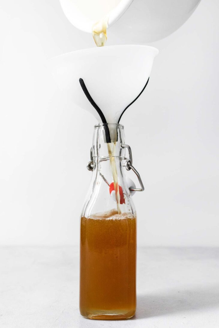 Pouring honey syrup into a glass container.