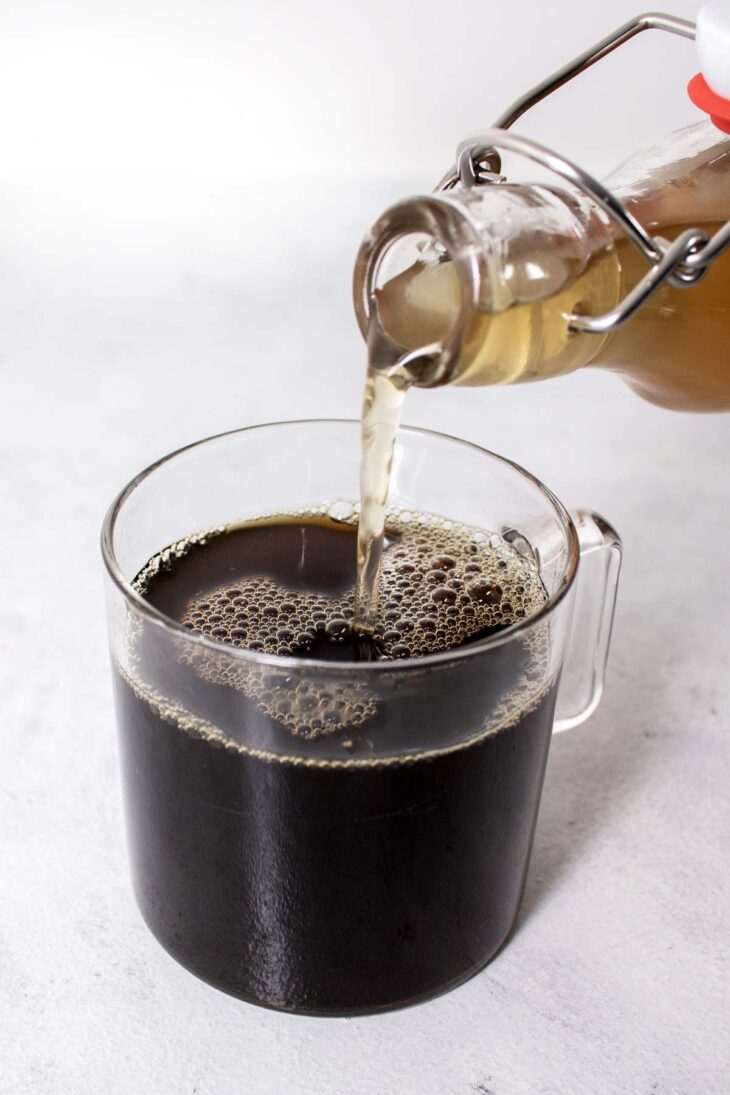 Pouring honey syrup into a cup of coffee.