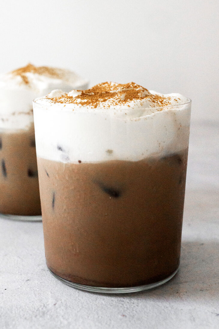 Two cups of iced Mexican coffee with cream topping.