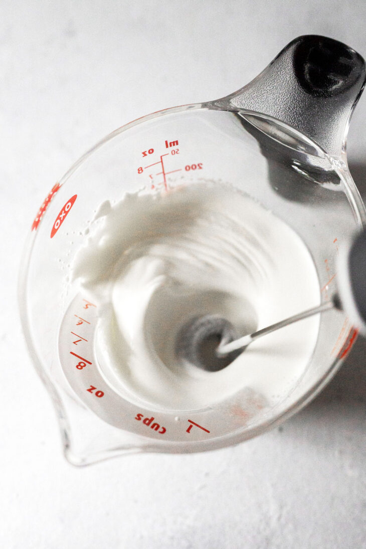 Whisking heavy cream to make whipped cream.