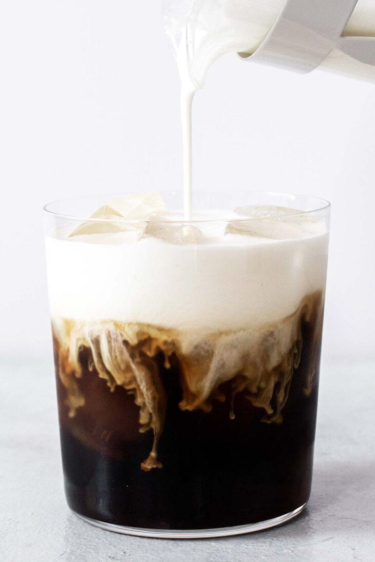 Pouring cold foam onto Irish Cream Cold Brew.