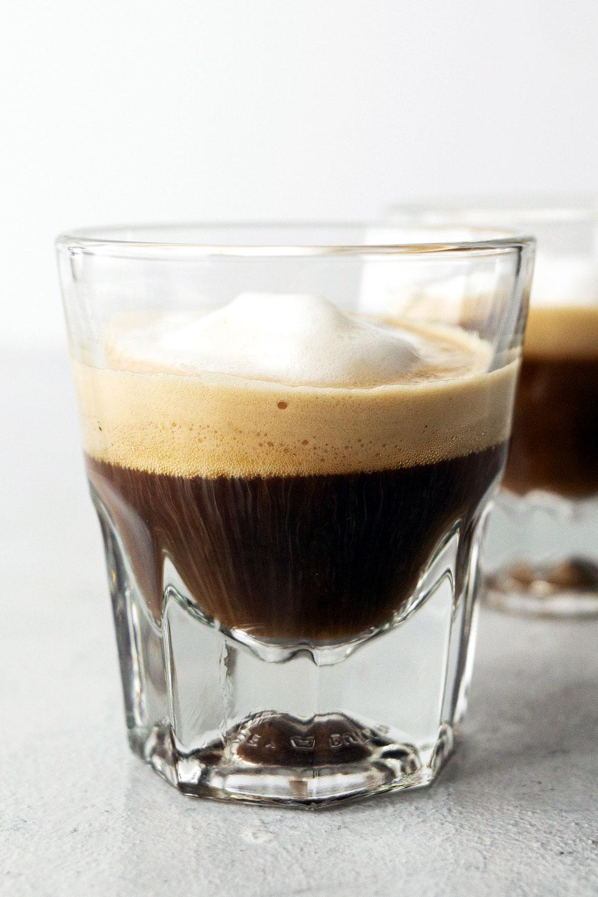 Espresso macchiato in a glass cup.
