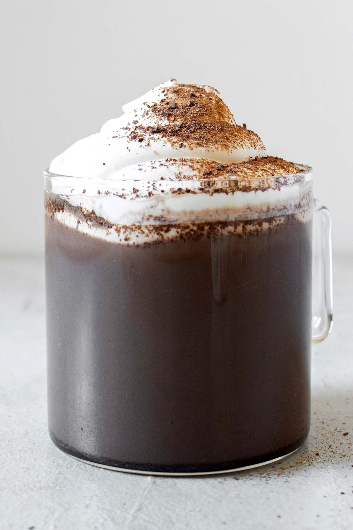 Mexican hot chocolate in a glass cup with whipped cream, garnished with grated chocolate and ground cinnamon.