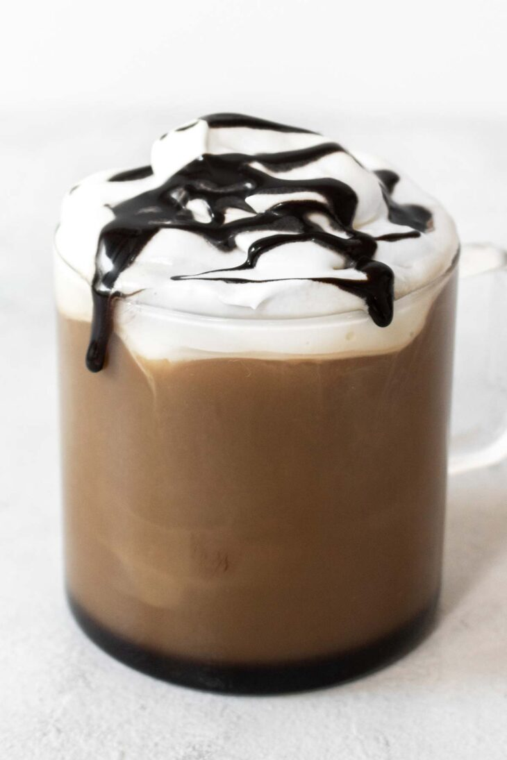 Mocha drink in a glass mug with whipped cream and chocolate drizzle.