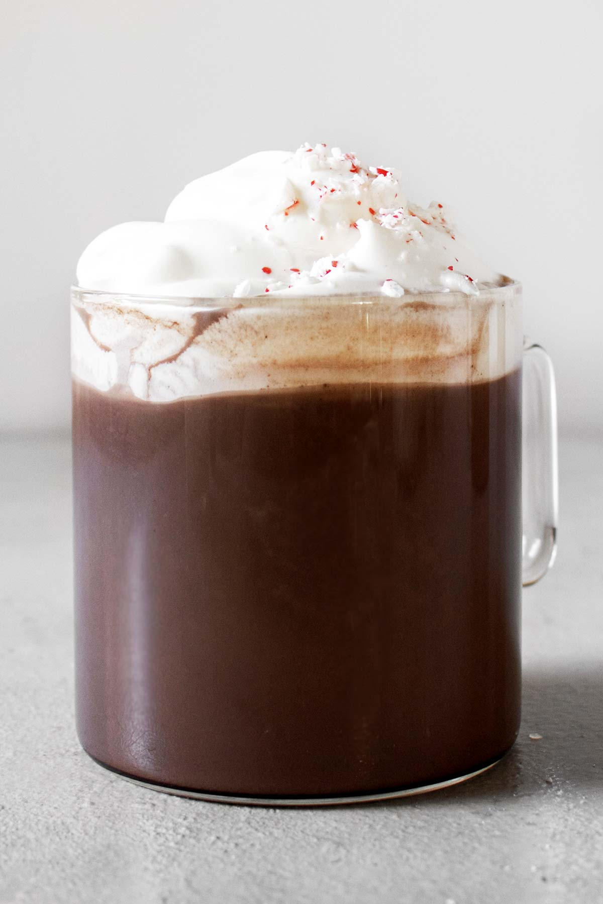Peppermint hot chocolate in a glass mug with whipped cream and crushed candy cane.
