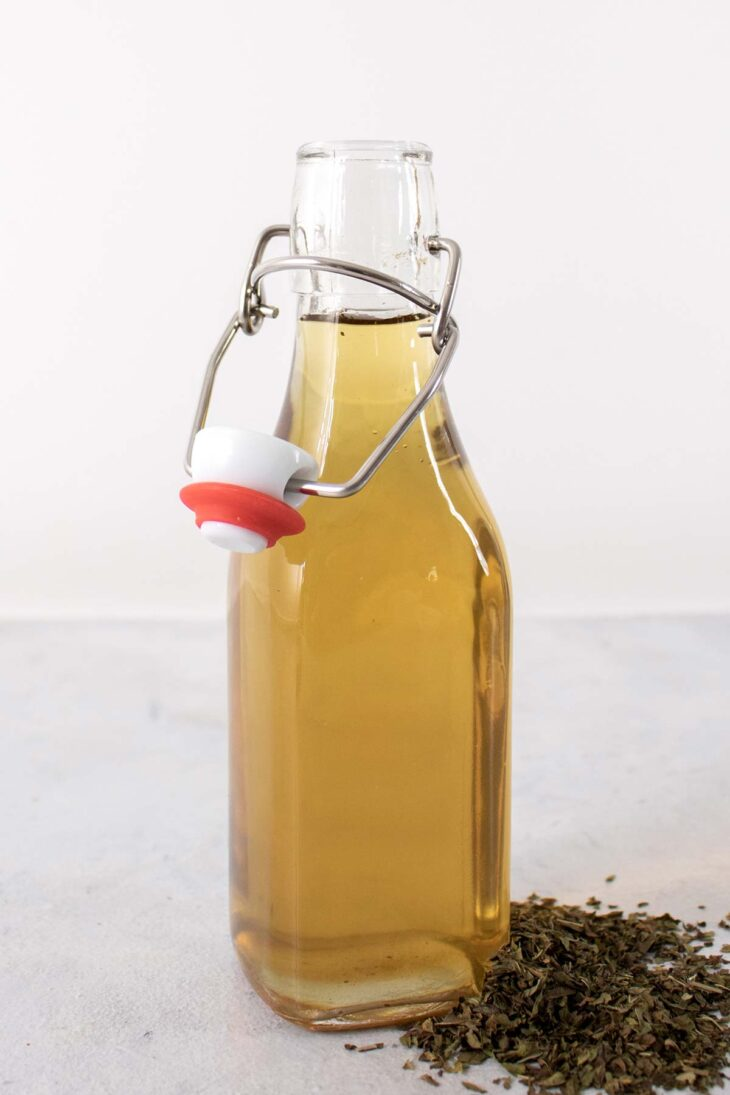 Mint simple syrup in a glass bottle.