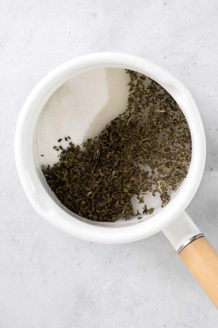 Water, sugar, and peppermint tea in a saucepan.