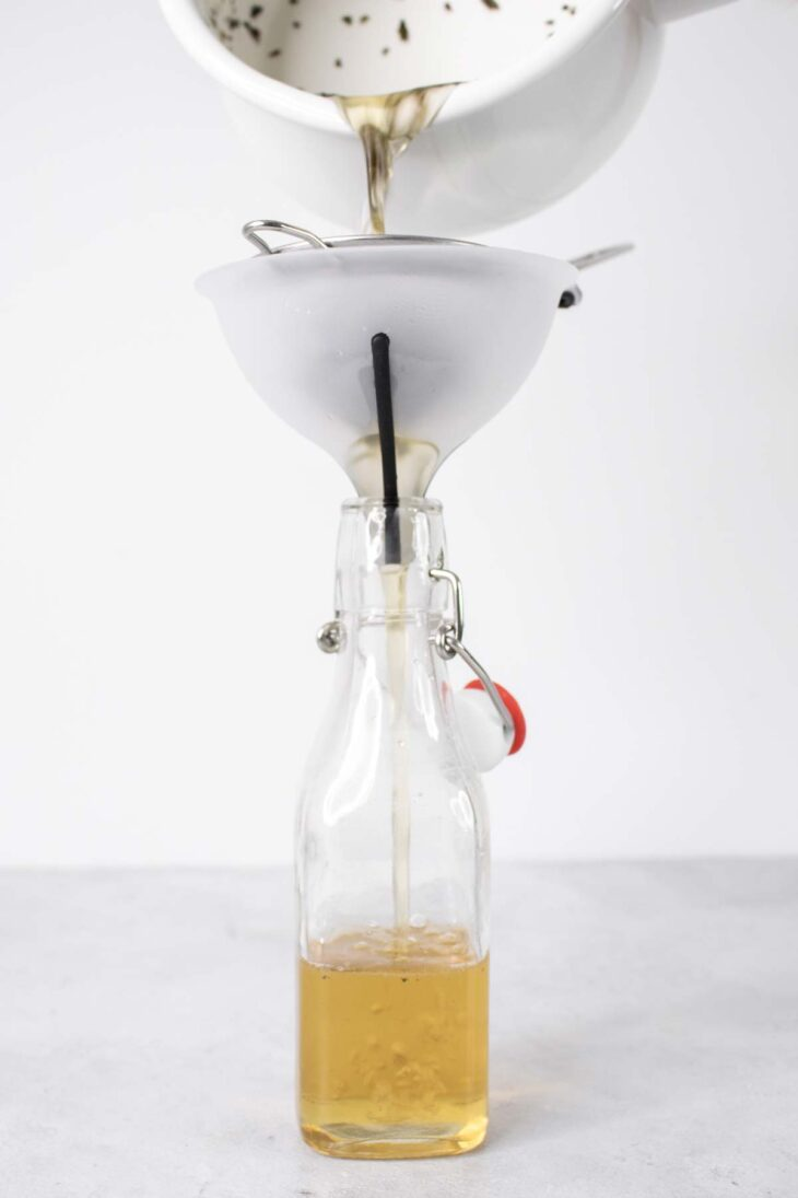 Pouring mint simple syrup into a glass bottle from a saucepan.