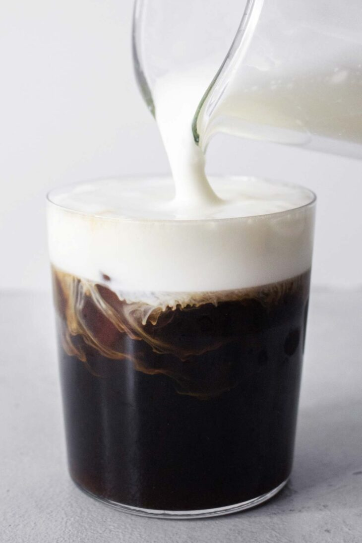 Pouring cream topping onto a pumpkin spiced cold brew coffee.