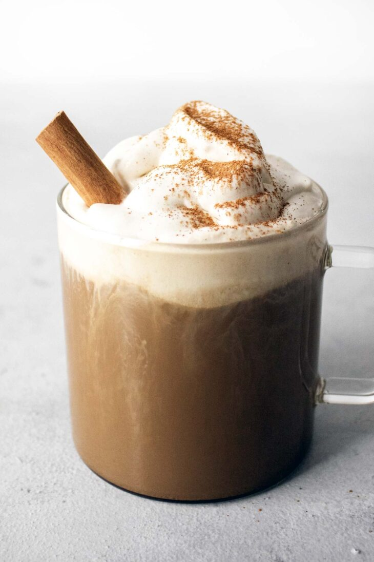 Pumpkin spice latte in a glass with whipped cream and a cinnamon stick.