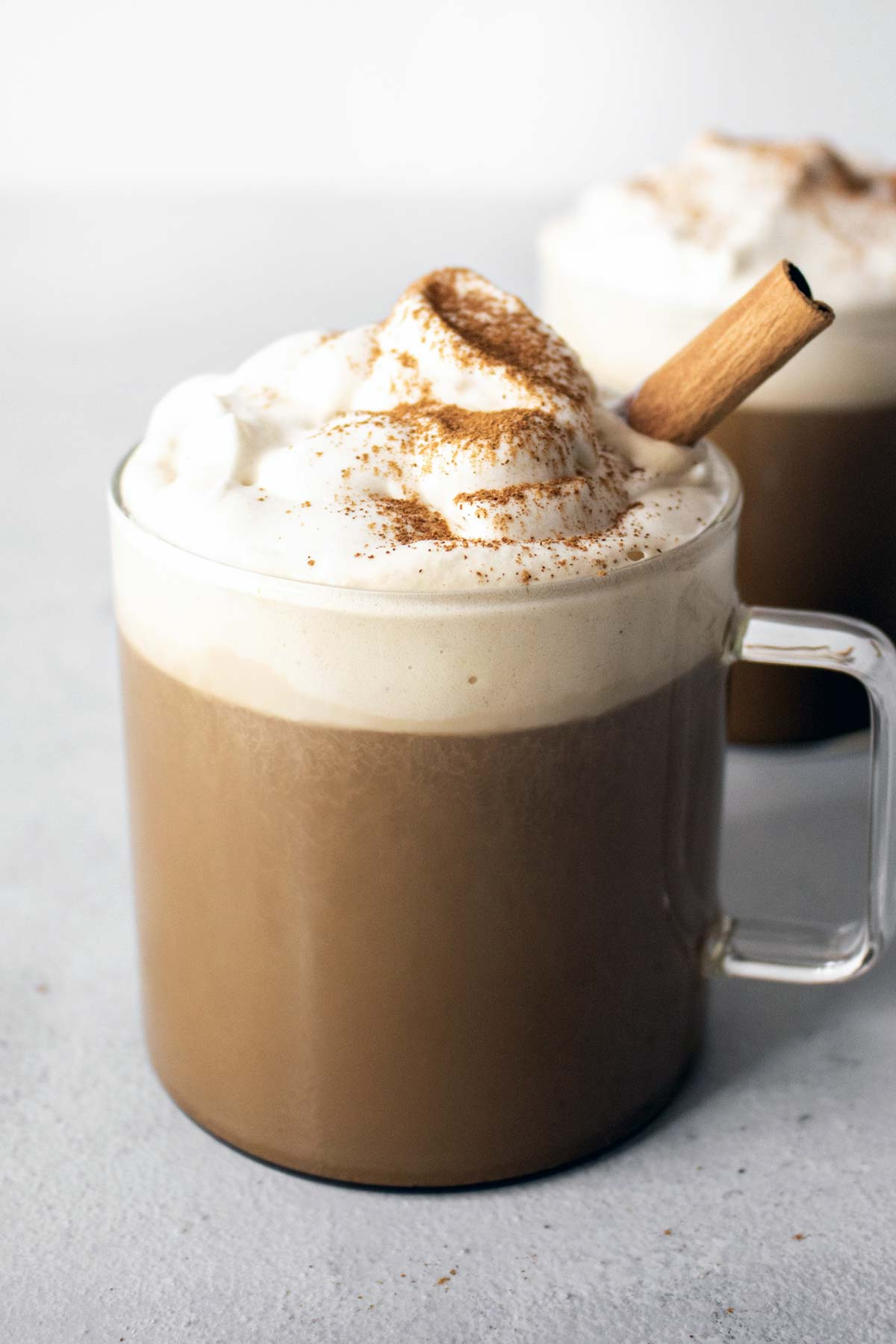 Pumpkin spice latte in mugs with whipped cream and cinnamon stick garnish.