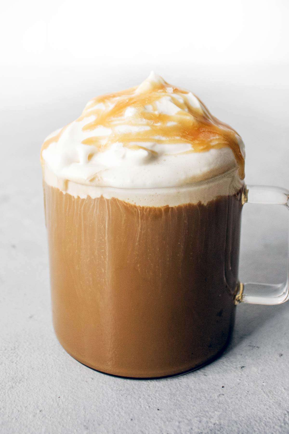 Salted caramel latte topped with whipped cream and caramel drizzle in a glass mug.