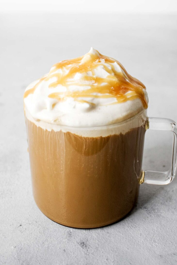 Salted caramel latte in a glass mug.