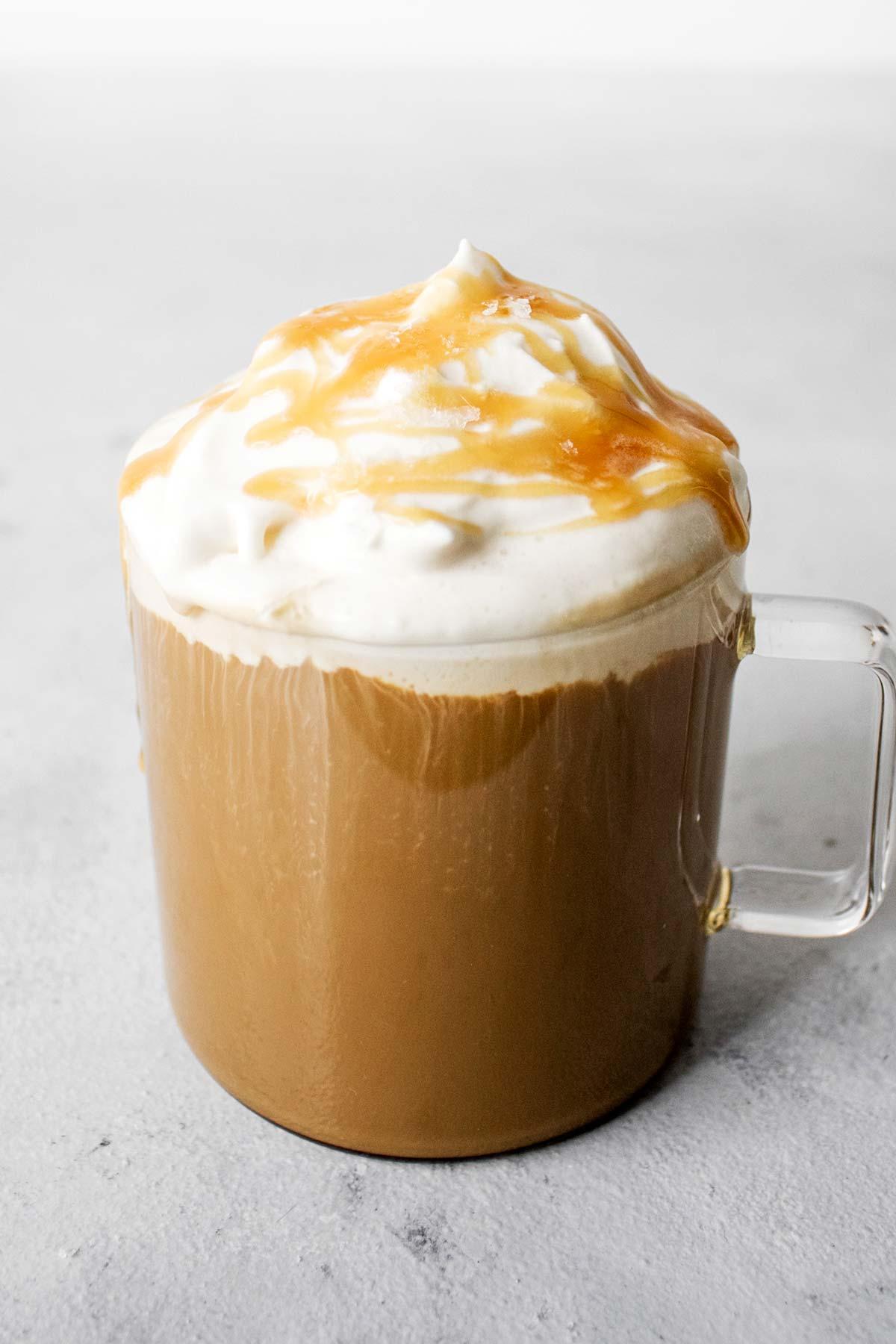 Salted caramel latte in a glass mug.