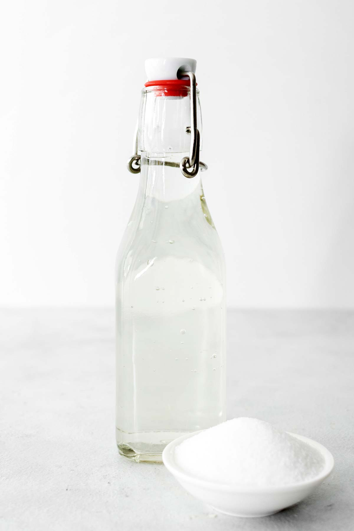 Homemade simple syrup in a glass bottle with a little bowl of granulated sugar.