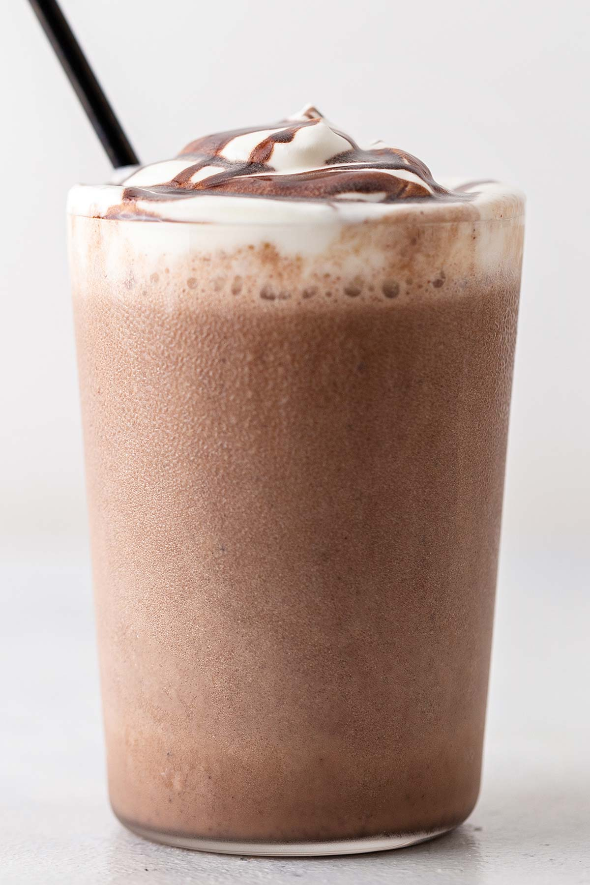 Double Chocolaty Chip Frappuccino in a cup with whipped cream and chocolate drizzle.
