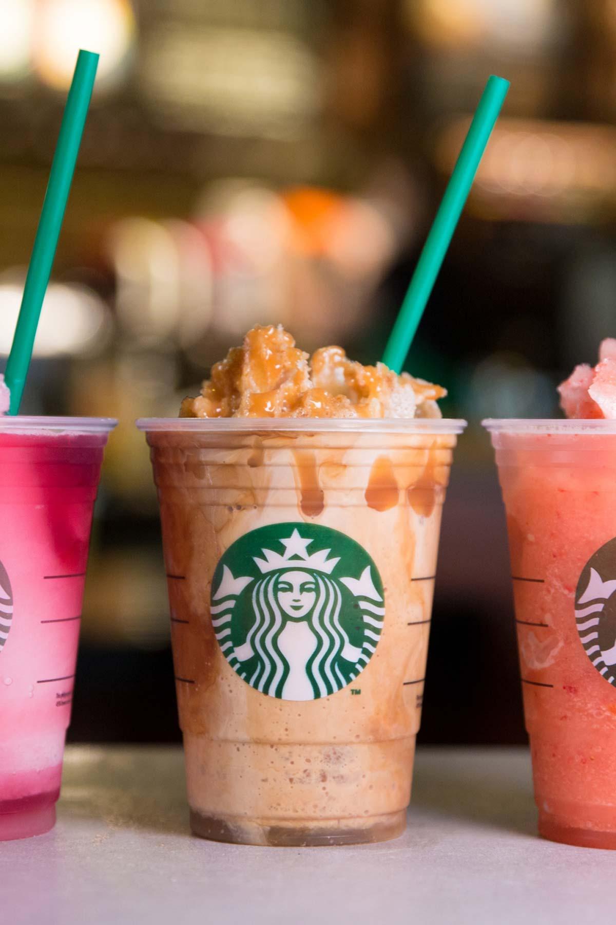 Three Starbucks drinks with green straws.