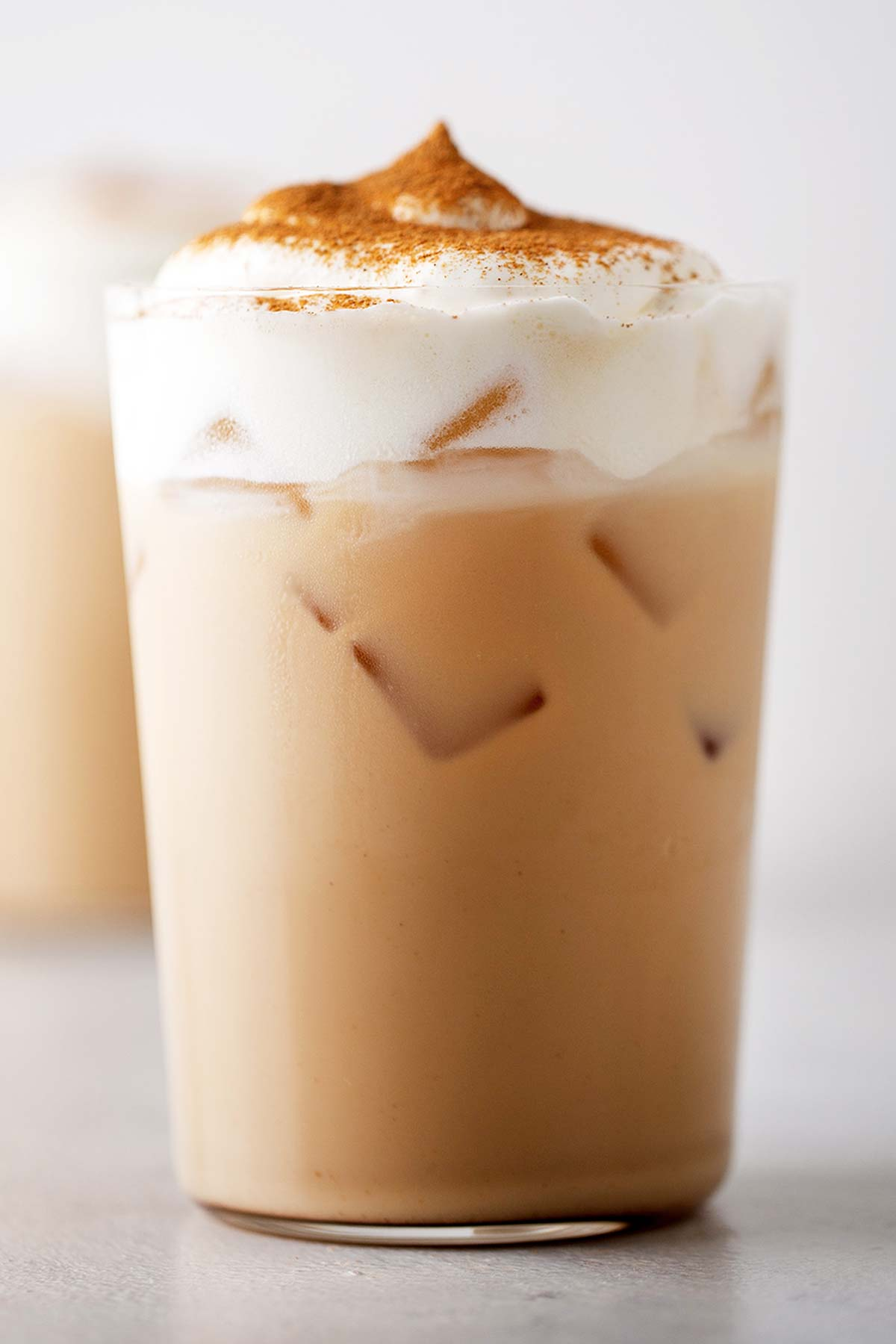 Iced Pumpkin Spice Latte in a cup with whipped cream.