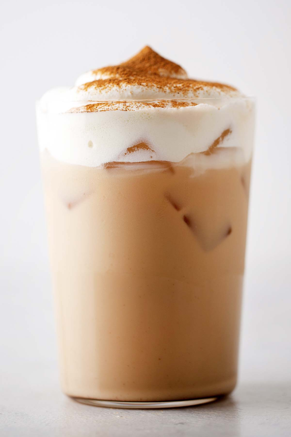Iced Pumpkin Spice Latte drink in a cup with whipped cream.