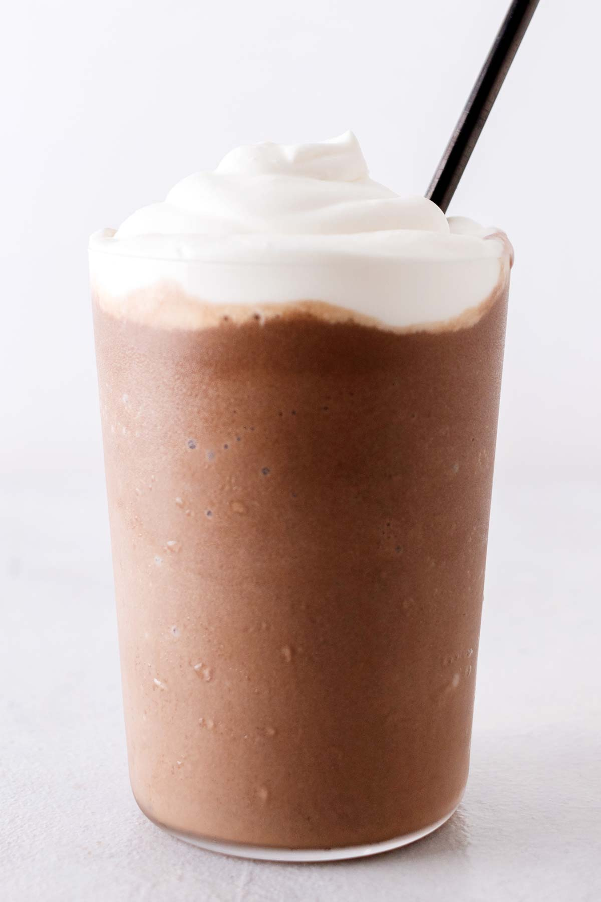 Homemade Mocha Frappuccino drink in a cup with whipped cream.