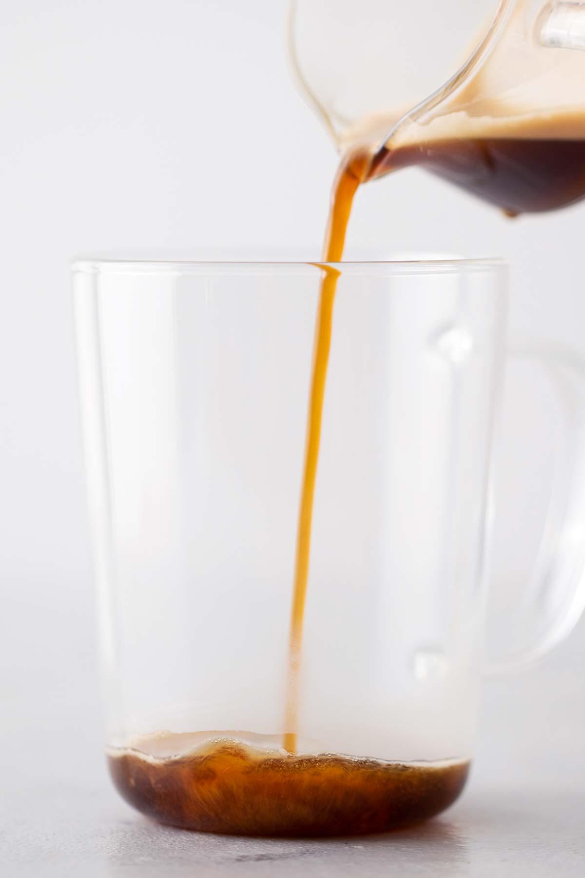 Pouring espresso into a glass mug.
