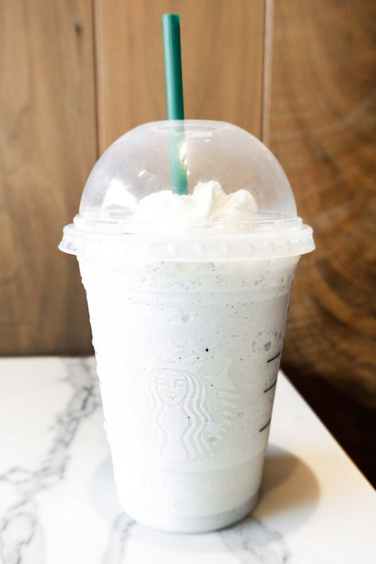 Starbucks Cotton Candy Frappuccino in a cup with whipped cream and a green straw.