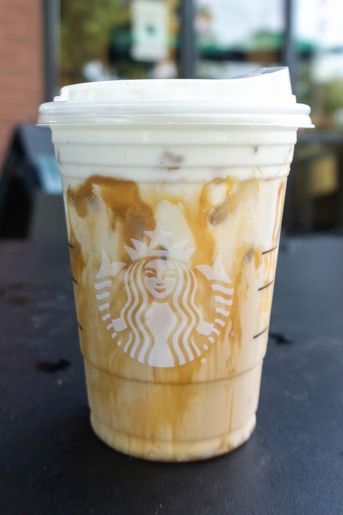Iced White Mocha with Sweet Cream Foam with extra caramel drizzle Starbucks drink in a cup.