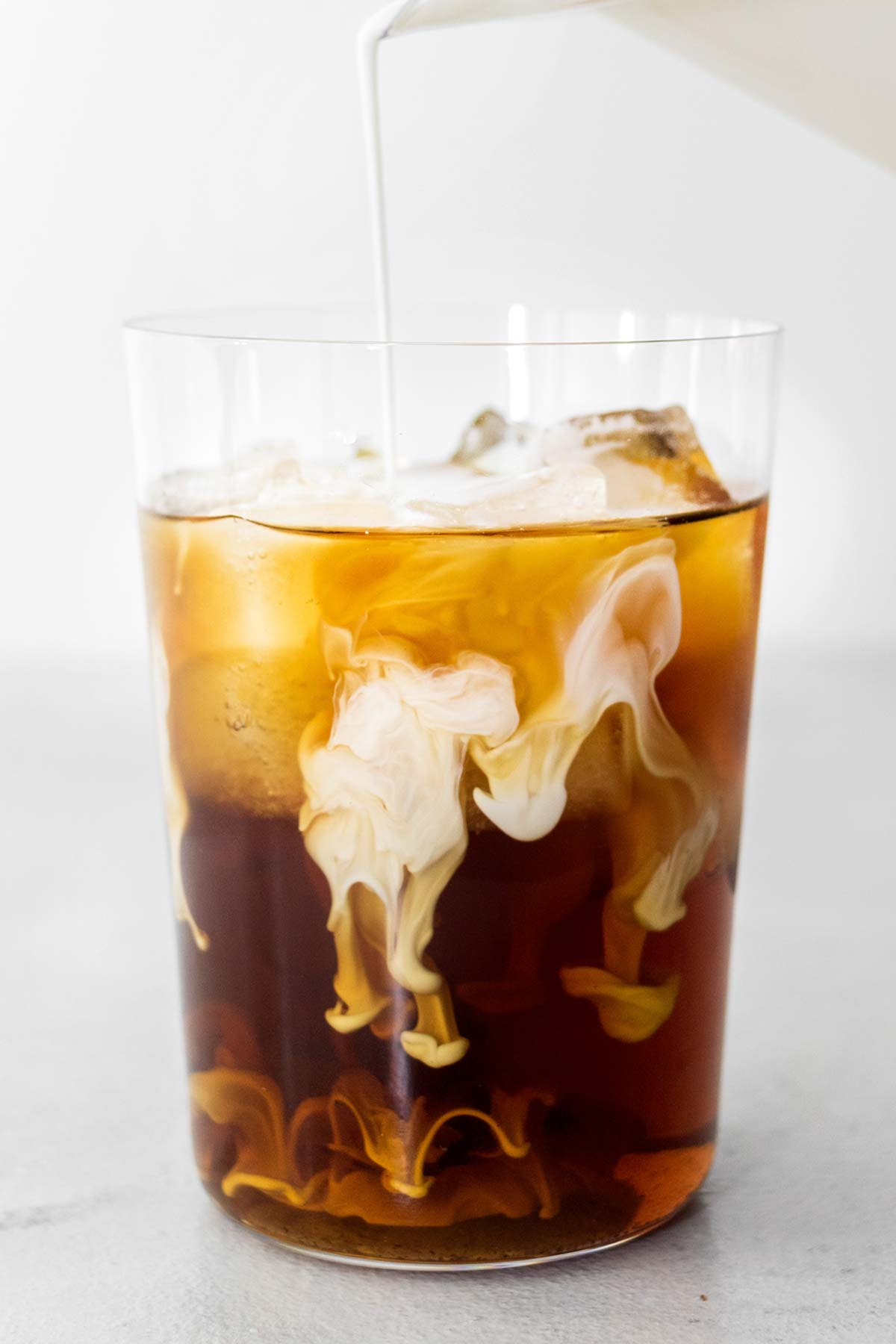 Pouring Sweet Cream into a cup of cold brew coffee with ice.