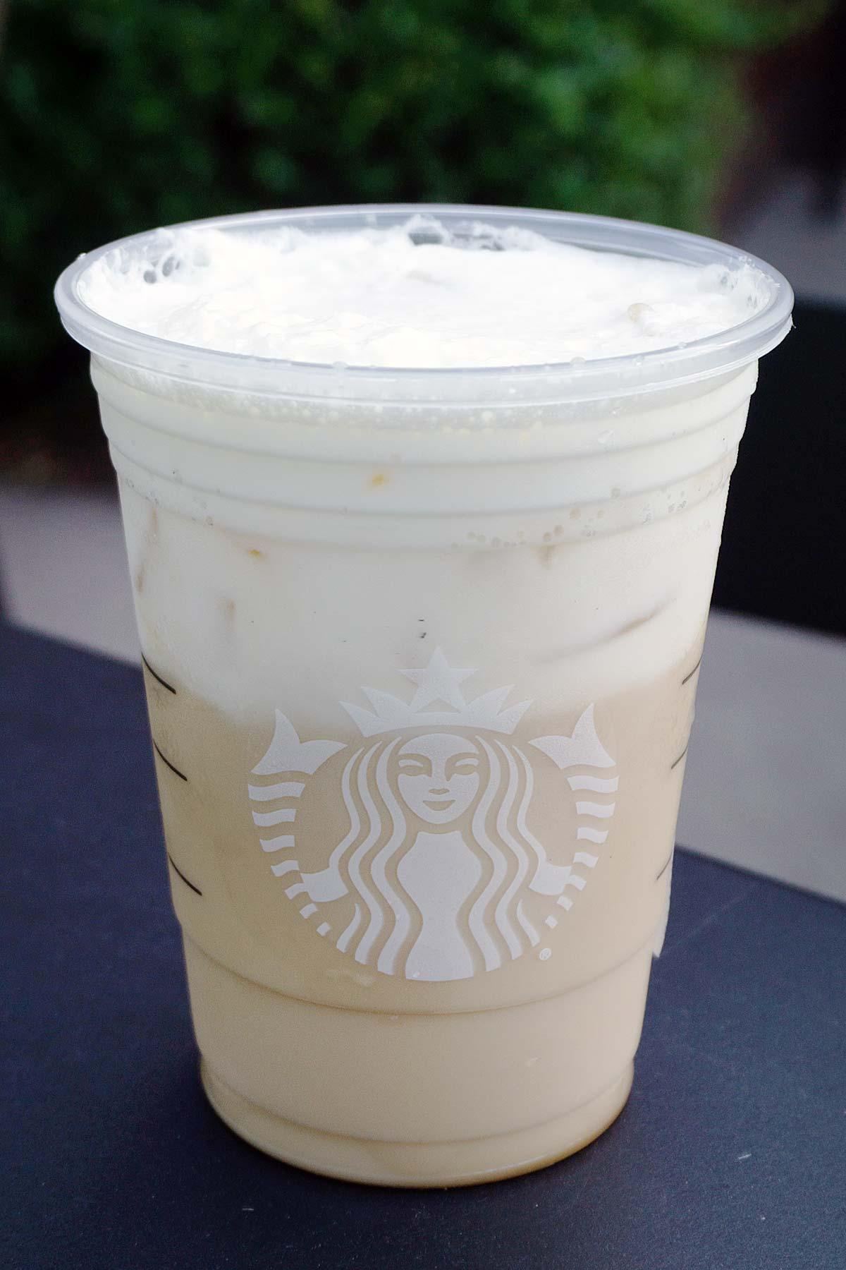 A TikTok Iced Chai Latte drink in a plastic Starbucks cup.