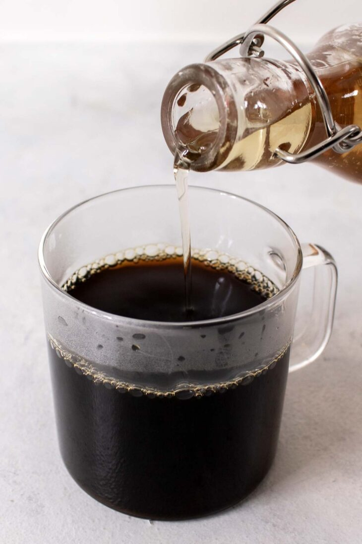 Pouring vanilla simple syrup into a cup of coffee.